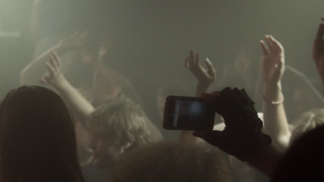 SLO MO man taking photo with mobile phone in crowded nightclub, talking to woman / New York, New York