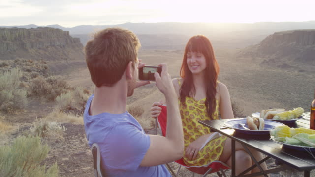 MS Man taking photo with smartphone of smiling woman sitting at portable table near desert canyon