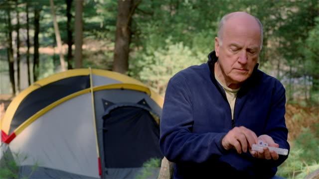 MS, man taking taking pill sitting at camping site, USA, Pennsylvania, Solebury