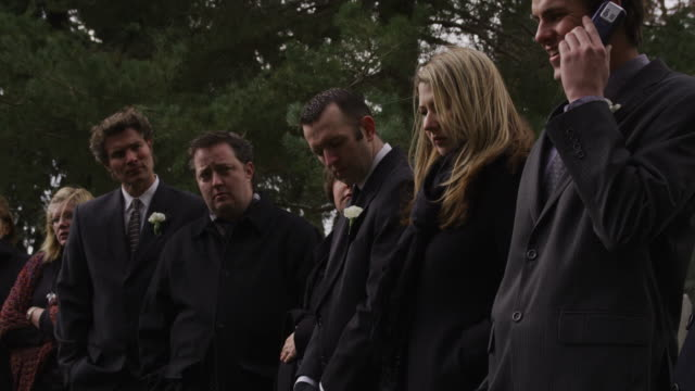 man talking on his cell phone at a funeral