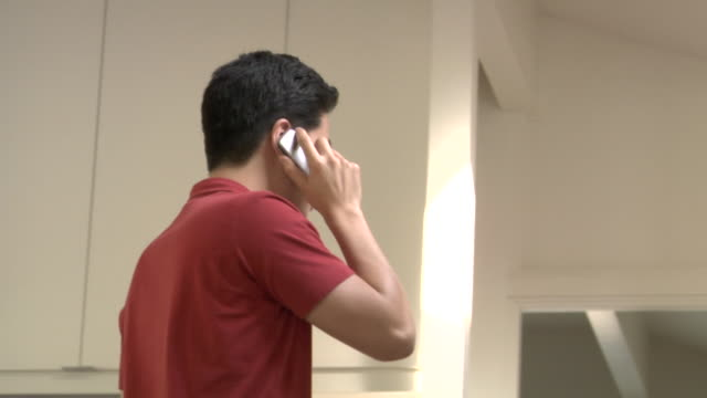 MS, Man talking on mobile phone in kitchen