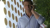 CU LA Man talking on mobile phone office building and tree in background / Miami, Florida, USA