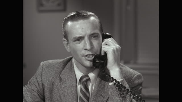 CU Man talking on telephone with serious expression in office / United States