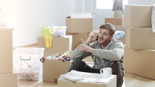 Man talking on the phone and holding cup of coffee in his new apartment full of unpacked boxes