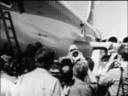 B/W 1970 man talking thru megaphone to crowd by parked airliner hijacked by PLO terrorists / Jordan