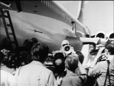 B/W 1970 man talking thru megaphone to crowd by parked airliner hijacked by PLO terrorists / Jordan