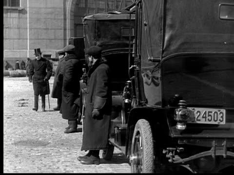 B/W, MS, Man talking to cab drivers waiting on street, 1924