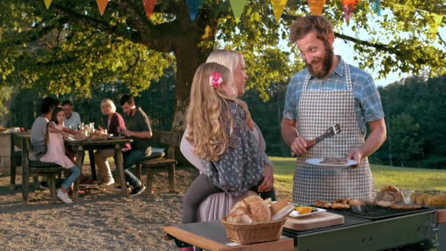 SLO MO Man aan zijn vrouw en zijn dochter praten tijdens het barbecueën
