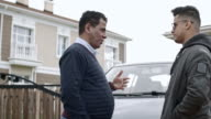 Man talking to teenage son about car driving