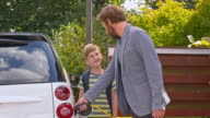 DS Man talking with son while plugging in electric car