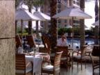 Man talks on mobile phone by poolside of luxury hotel Dubai