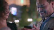 Man talks with friends and looks at smartphone on night out in Las Vegas.