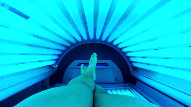 Man tanning in solarium