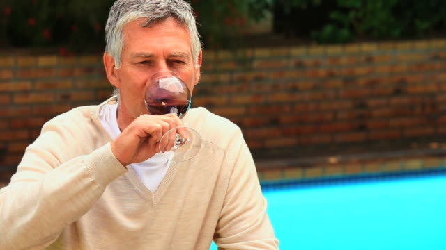 Man tasting a glass of red wine / Cape Town, Western Cape, South Africa