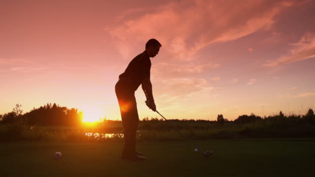 Man tees off at sunrise