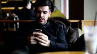 Man texting op smartphone in een café