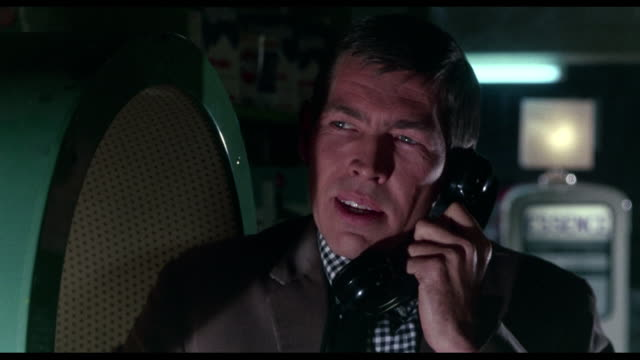 Man (James Coburn) threatens someone on telephone