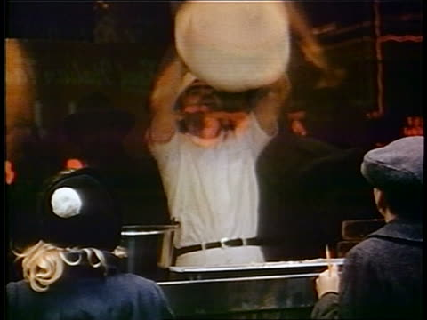 1958 man throwing pizza dough over head in pizzeria / children watching thru window in foreground