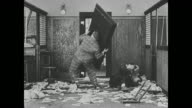 Fatty Arbuckle throws a door on top of a group of bank robbers who are then chased by Fatty Arbuckle and Buster Keaton