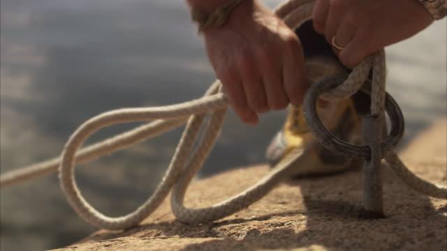 A man ties up a knot Blido Sweden.