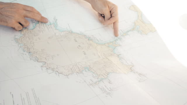 A man tracks a route in a paper map of Ibiza Island.