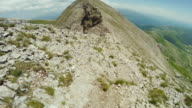 Man trail running on a dangerous ridge POV