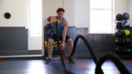 Man Training in Gym with Battle Ropes