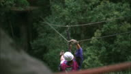 Man travels along zip line towards wooden platform in forest, Tsitsikamma National Park. Available in HD.