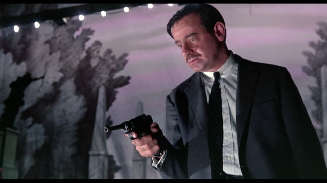Man (Walter Matthau) treads the stage trapdoors in pursuit of frightened woman (Audrey Hepburn) as another man (Cary Grant) waits to trap him