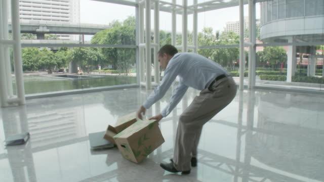 MS PAN Man tripping and dropping cardboard boxes in lobby / Bangkok, Thailand
