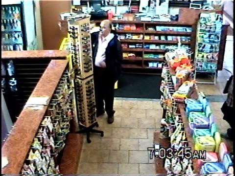 HA WS Man trying on sunglasses in convenience store, then looks around, puts pair into his jacket and walks away without paying for them / Brooklyn, New York, USA