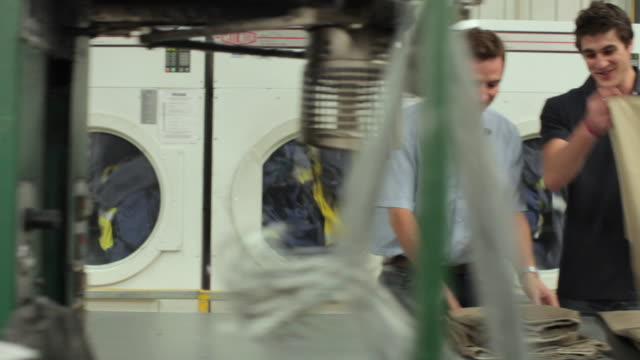 MS PAN Man turns on industrial dryer and walks to colleague who is folding clothes / Perth, Western Australia, Australia