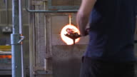 A man twists a glass object on the end of a blowpipe in a furnace, UK.