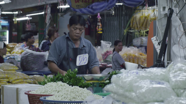 LS man tying bunches of green leaves in flower market, RED R3D 4K