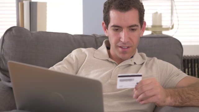 Man typing in credit card information on laptop
