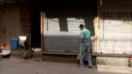 A man unlocks and opens a shop shutter.