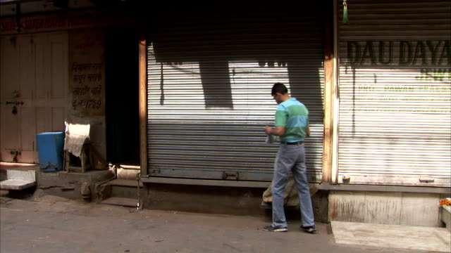 A man unlocks and opens a shop shutter.