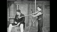 Buster Keaton, upset at a strongman's treatment of his assistant, hits the strongman's head with the backside of an ax, and then the front side, but it doesn't harm him, and the strongman (Charles A. Post) pushes Keaton