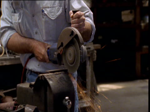 Man uses angle grinder in workshop, Tasmania