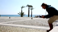 Man uses digital tablet at beach