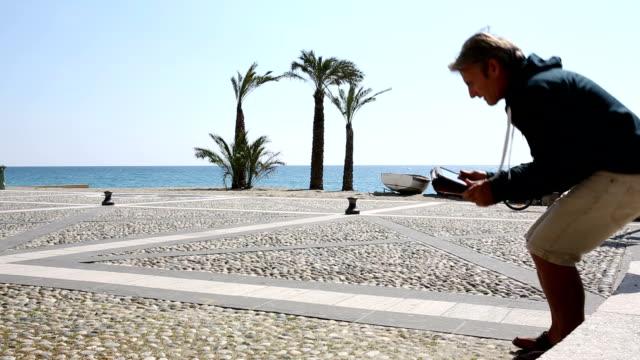 Man uses digital tablet at beach