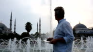 Man uses digital tablet, in front of Blue Mosque, Istanbul, Turkey