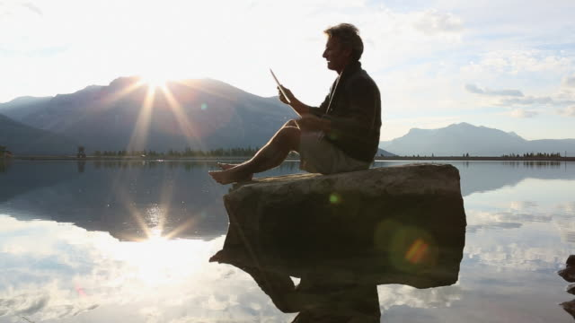 Man uses digital tablet while sitting on rock, by mtn lake