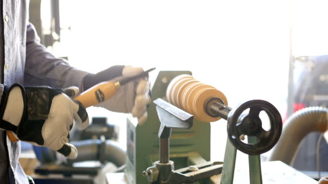 Man uses lathe in community woodworking workshop