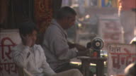 Man uses sewing machine on busy street as other talks on phone Rajasthan Available in HD.