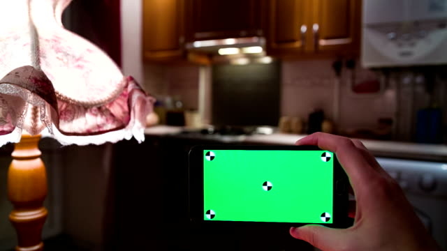Man uses smartphone at kitchen.