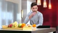 Mann mit digitalen Tablet während des Frühstücks