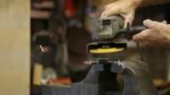 Man using a grinder in his workshop.