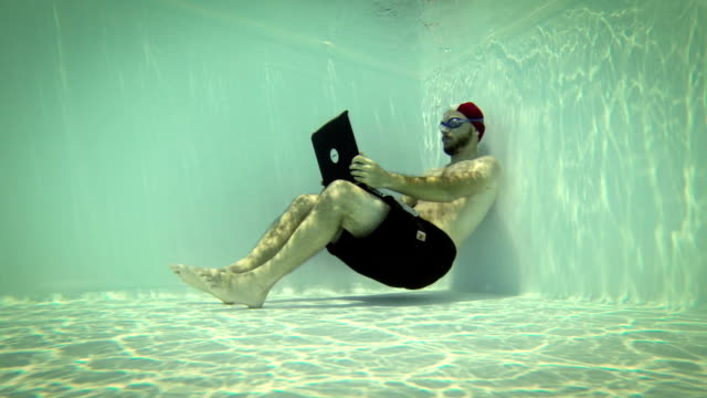 Man using a laptop underwater