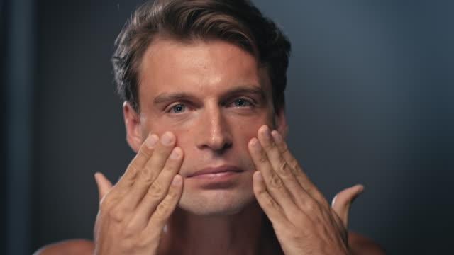 Man using creme on his face